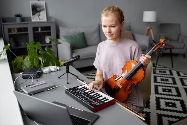 Kobieta grająca na skrzypcach przy biurku, średni strzał