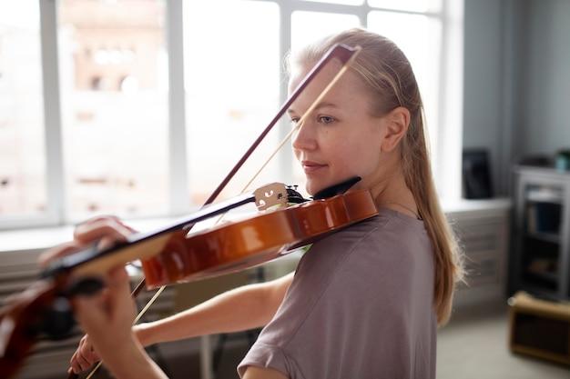 Kobieta grająca na skrzypcach średni strzał