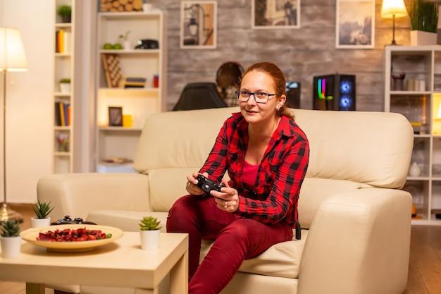 Kobieta grająca w gry wideo na konsoli w salonie późno w nocy