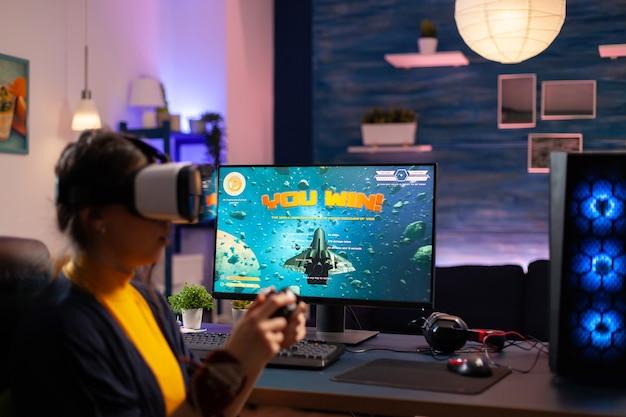 Kobieta grająca w gry wideo z zestawem słuchawkowym vr na potężnym komputerze z profesjonalnym joystickiem. wirtualne cyberprzesyłanie strumieniowe online podczas turnieju gry przy użyciu nowoczesnego sprzętu.