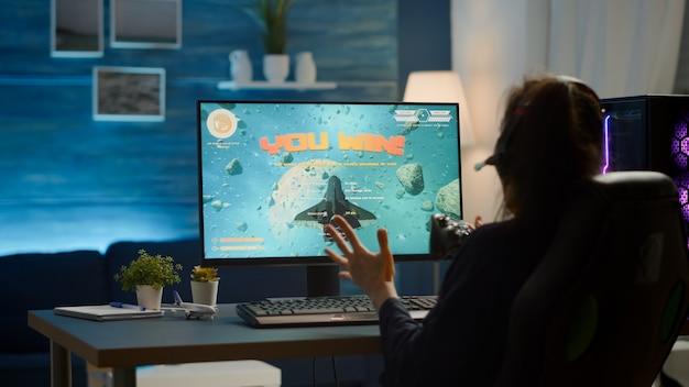 Kobieta grająca w gry wideo za pomocą profesjonalnego bezprzewodowego kontrolera i zestawu słuchawkowego grająca na potężnym komputerze. podekscytowany cyberprzesyłanie strumieniowe online podczas turnieju gier za pomocą joysticka.