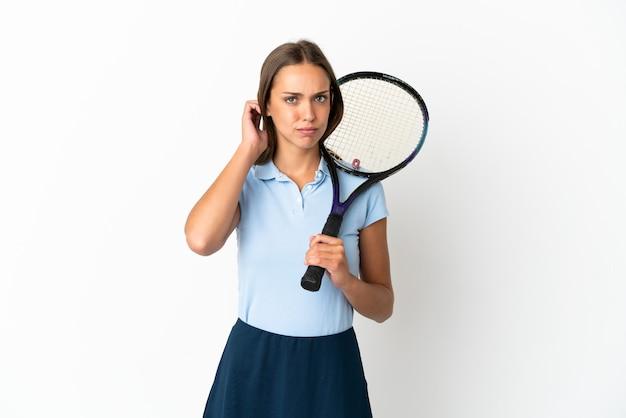 Kobieta grająca w tenisa na odosobnionej białej ścianie, która ma wątpliwości