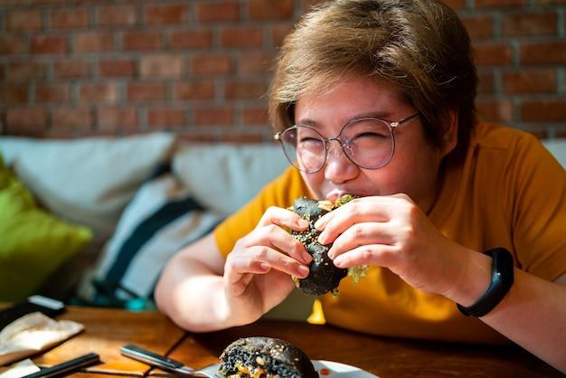 Kobieta gryzie burgera z brokułami quinoa i guacamole