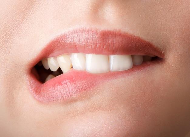Kobieta gryzie swoje czerwone usta zębami