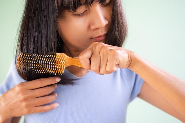 Kobieta grzebień do ramion. czesanie jej włosów. autentyczny dopasowany krój, czarne włosy i opalona skóra dla dorosłych azjatyckich tajlandii. styl życia wakacje w domu dla mody urody i dobrej koncepcji zdrowia.