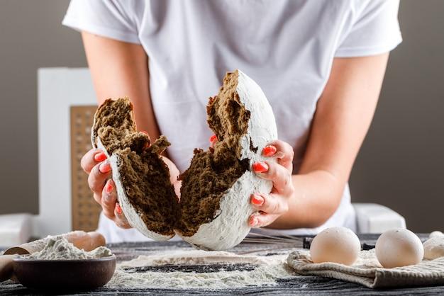 Kobieta hamowanie ciasto na pół z pinami jaj, mąka na ciemnym drewnianym stole widok z boku