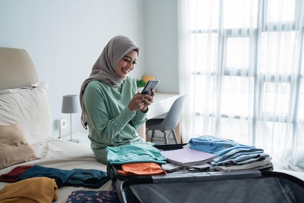 Kobieta hidżab sprawdzanie harmonogramów wyjazdu za pośrednictwem aplikacji na smartfony