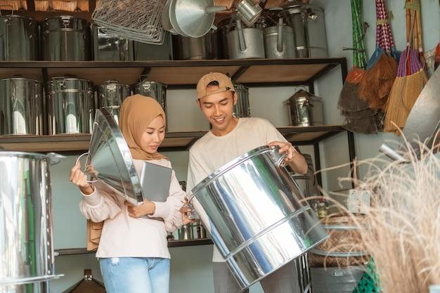 Kobieta hidżab stoi przy użyciu tabletu po otwarciu przykryj dużą patelnię mężczyzną trzymającym dużą patelnię w sklepie ze sprzętem agd