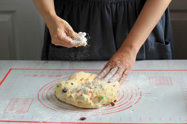 Kobieta home baker posyp mąką, aby uniknąć kleistego ciasta, wyrabianie ciasta chlebowego z rodzynkami i suszonymi owocami, proces przygotowywania świątecznych stollen niemiecki tradycyjny chleb