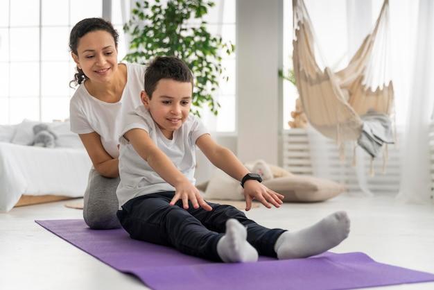 Kobieta i chłopak na matę do jogi pełny strzał