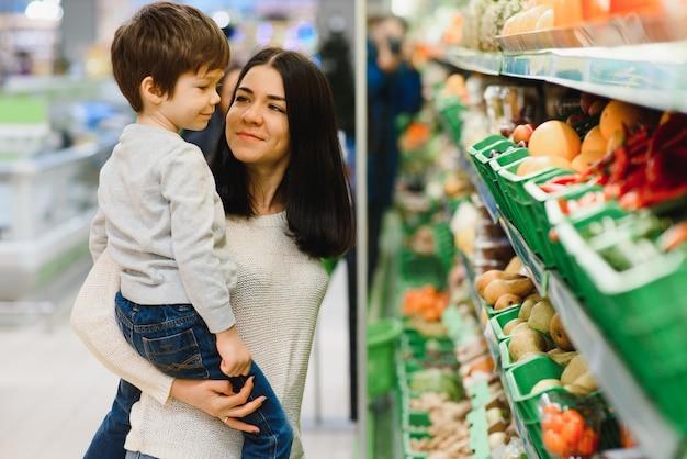 Kobieta i chłopiec dziecko podczas rodzinnych zakupów z wózkiem w supermarkecie