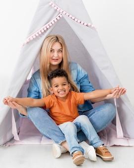 Kobieta i chłopiec pozuje razem w namiocie