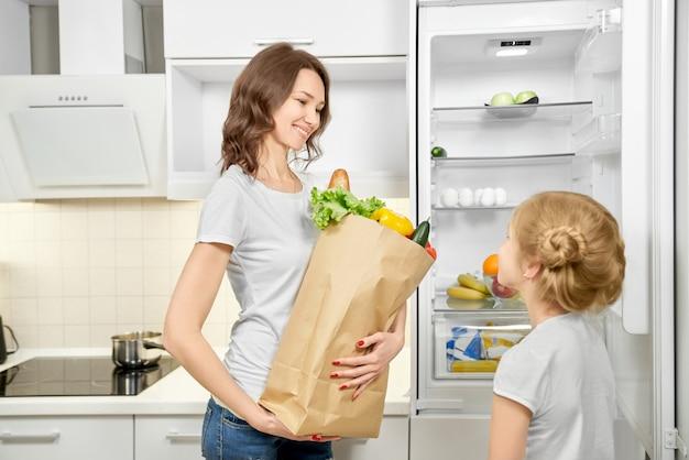 Kobieta i córka z produktami torba w pobliżu pustej lodówki.