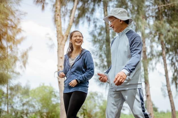 Kobieta i dziadek spacerują po ulicy w parku rozmowa dziadka