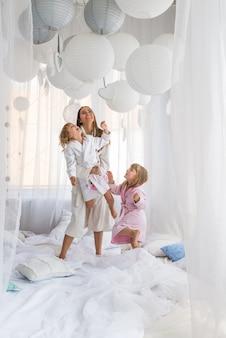 Kobieta i dzieci na łóżku