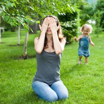 Kobieta i dziecko bawią się w chowanego w wiosennym parku