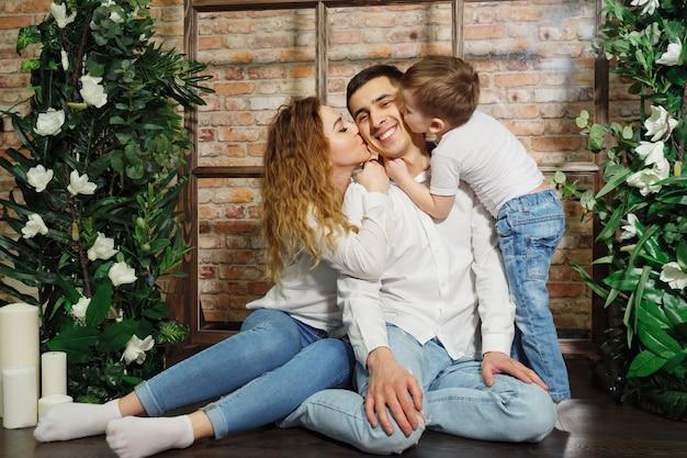 Kobieta i dziecko całuje człowieka. szczęśliwa rodzina w codziennych ubraniach