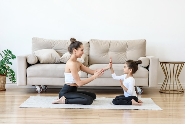 Kobieta i dziecko dziewczynka bawić się razem w domu w pobliżu sofy w salonie