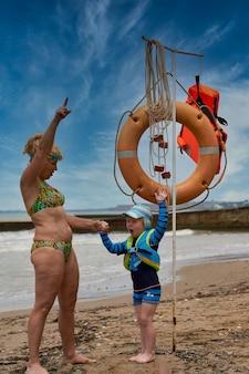 Kobieta i dziecko obok ratunku stoją nad morzem. bezpieczne rodzinne wakacje na morzu