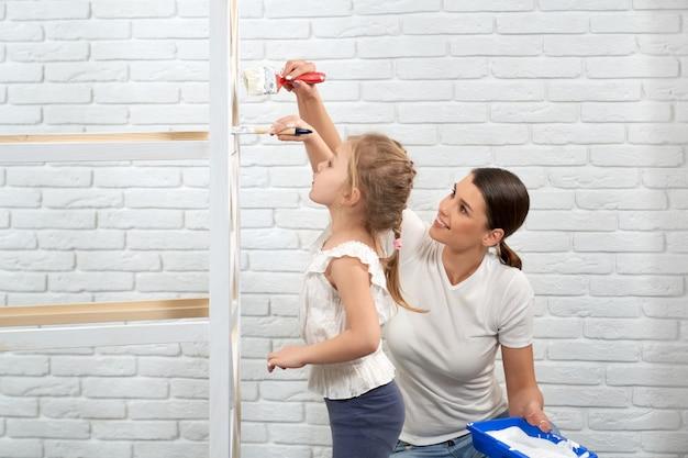 Kobieta i dziecko odświeżają drewniane półki z białą farbą