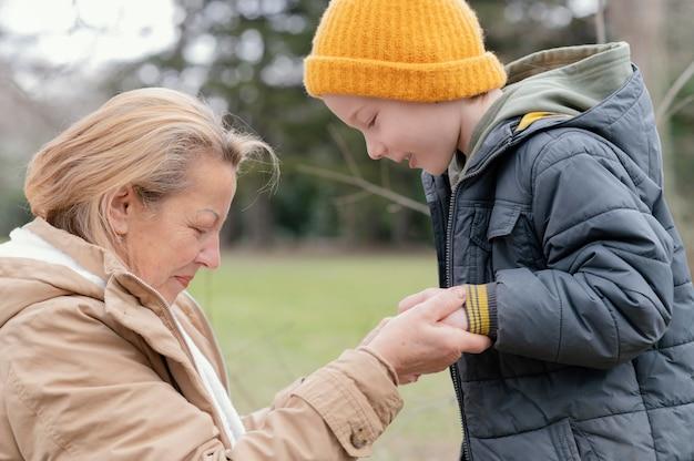 Kobieta i dziecko trzymając się za ręce średni strzał