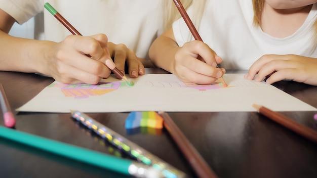 Kobieta i dziewczyna bez twarzy malują ołówkami na papierze, siedząc przy stole w domu