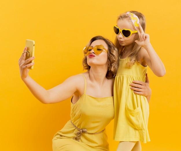 Kobieta i dziewczyna biorąc selfie podczas noszenia okularów przeciwsłonecznych