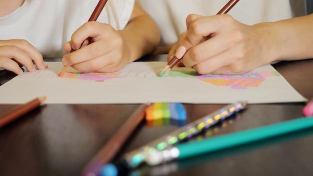 Kobieta i dziewczyna malują kredkami na papierze siedząc przy stole w domu