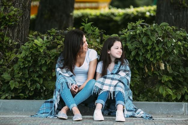 Kobieta i dziewczyna siedzi na ulicy krawężnika