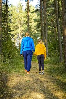 Kobieta i dziewczyna wędrówki leśną drogą w słoneczny dzień