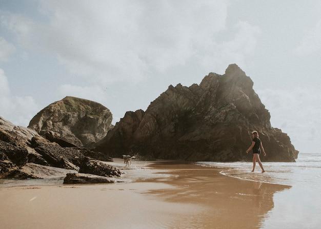 Kobieta i jego pies bawią się na plaży