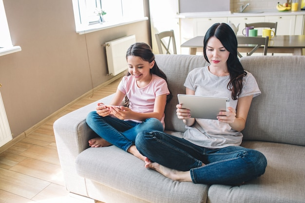 Kobieta i jej córka siedzą na kanapie ze skrzyżowanymi nogami i czytają