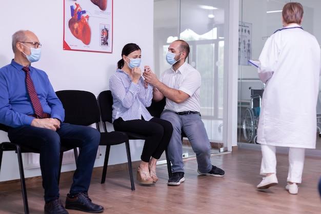 Kobieta i jej mąż płaczą w nowej normalnej szpitalnej poczekalni z powodu wyników badań klinicznych. personel medyczny podający niekorzystne wieści. zestresowany mężczyzna i kobieta podczas wizyty lekarskiej.