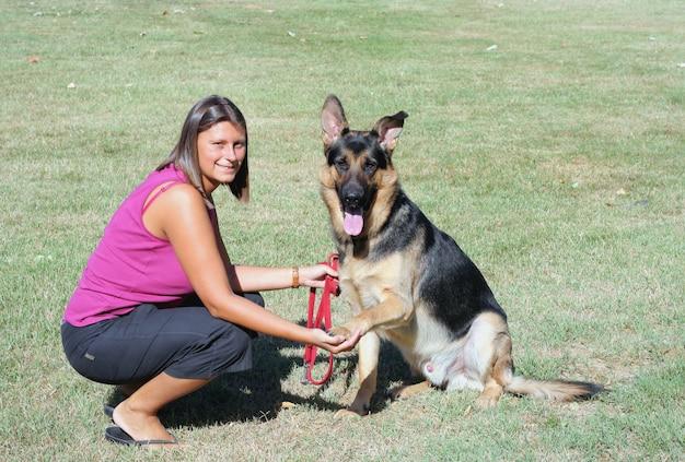 Kobieta i jej pies owczarek niemiecki w parku