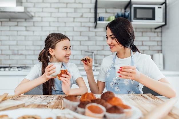Kobieta i jej śliczna córeczka w fartuchach uśmiechają się podczas degustacji babeczek