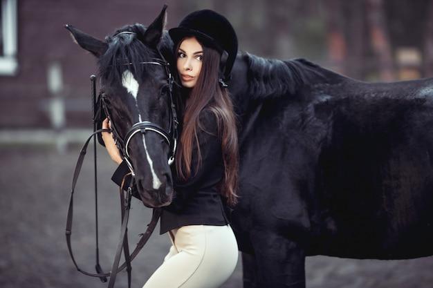 Kobieta i koń w szkole jeździeckiej