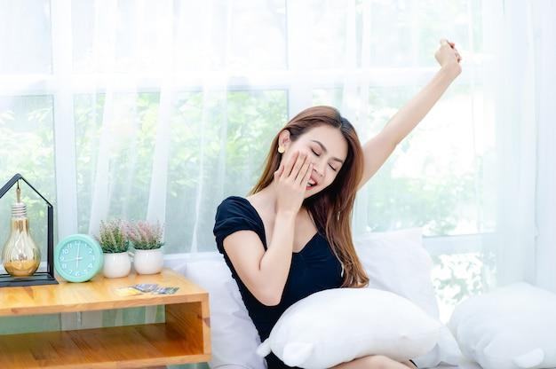 Kobieta i łóżko rano obudź się i szczęśliwie uśmiech dobre pojęcie odpoczynku