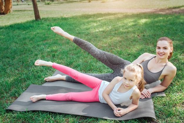 Kobieta i mała dziewczynka trzymają w powietrzu prawe nogi i opierają się na lewych rękach