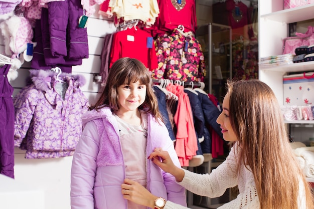 Kobieta i mała dziewczynka zakładają różową ciepłą kurtkę w sklepie odzieżowym