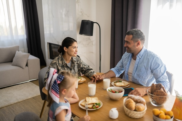Kobieta i mąż. wojskowa kobieta dotykająca ręki męża podczas rodzinnego śniadania