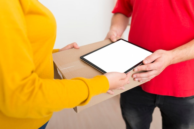 Kobieta i mężczyzna dostawy, trzymając pudełko i pusty tablet z ekranem