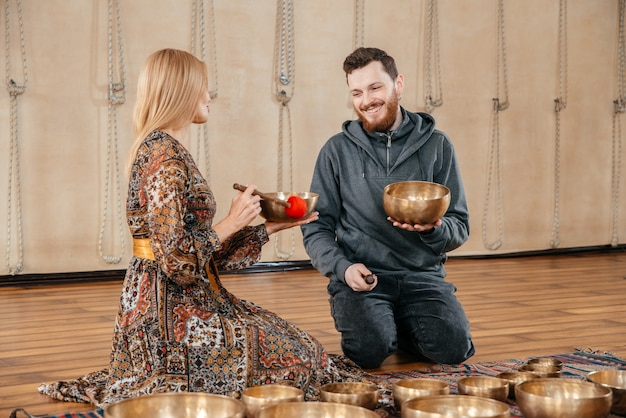 Kobieta i mężczyzna grający na tybetańskiej misce do terapii dźwiękiem na siedząco