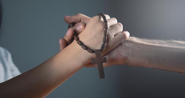 Kobieta i mężczyzna modlący się trzymający krzyż