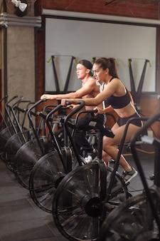 Kobieta i mężczyzna na rowerze w siłowni, ćwiczenia nóg robi trening cardio na rowerze