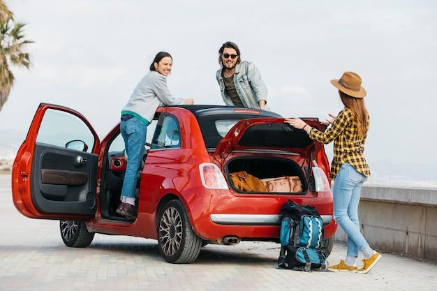 Kobieta i mężczyzna pochylony od samochodu w pobliżu pani z plecakiem w pobliżu bagażnika samochodu