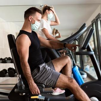 Kobieta i mężczyzna, poćwiczyć na siłowni z maskami medycznymi