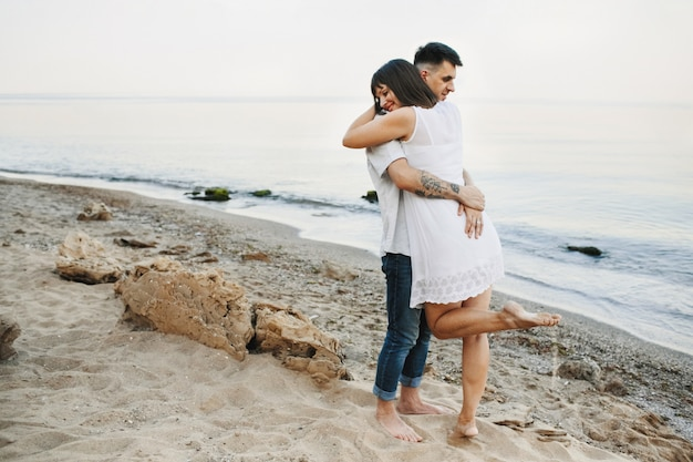 Kobieta i mężczyzna przytulają się na plaży w pobliżu morza