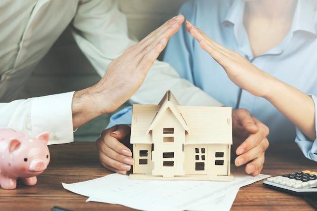 Kobieta i mężczyzna ręcznie modelu domu