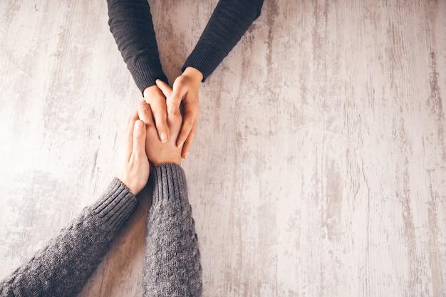 Kobieta i mężczyzna ręka w rękę na drewnianym stole