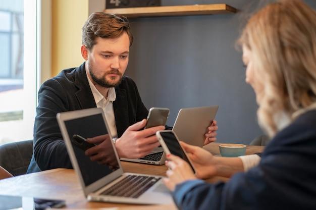 Kobieta i mężczyzna sprawdzają swój telefon na spotkaniu